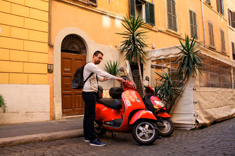 Italy Rome, man with scooter. man is ready to drive scooter in t. He city. Travel concept royalty free stock image