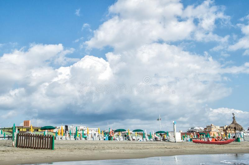 Italy, Rome, Ostia, Tyrrhenian Sea. Beginning / end of the beach season. The coastline is lined with folded umbrellas and sun beds. Large blue-white stock photography