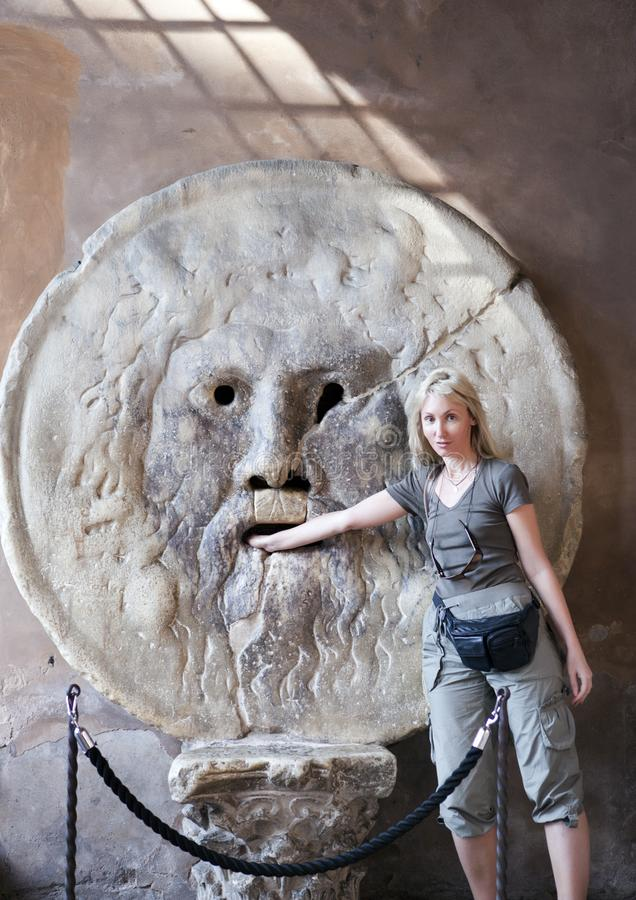 Italy. Rome. Woman tourist puts hand to mouth of truth royalty free stock image