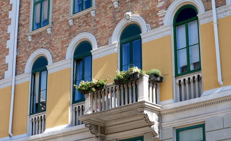italy trieste Facaden av ett gammalt hus Blommor på balkongen royaltyfria bilder