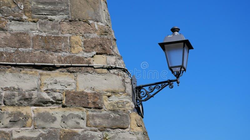 italy trieste Stenvägg av en forntida fästning och en lykta arkivfoto