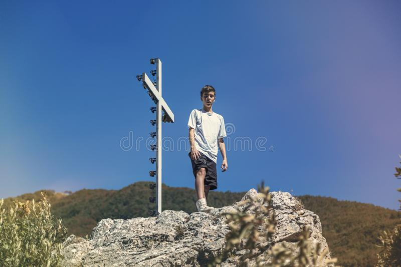 young man is standing next to a summit cross royalty free stock images