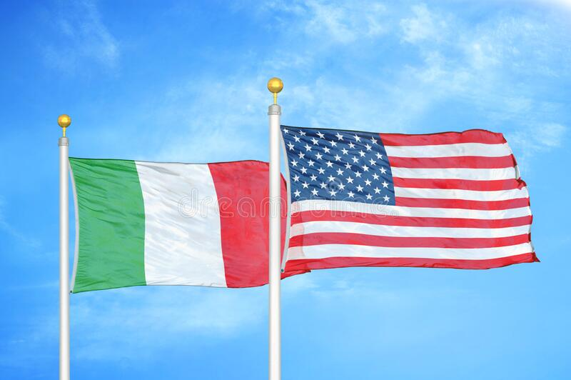 Italy and United States two flags on flagpoles and blue cloudy sky. Background royalty free stock photo