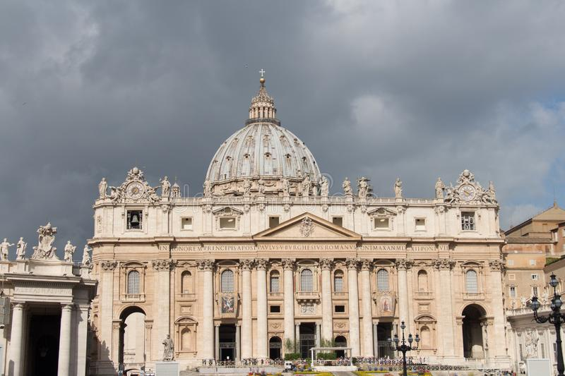 Main facade and dome of Saint Peter`s Basilica seen from Saint Peter`s Square with rainy clouds on background, Vatican city stat stock photos