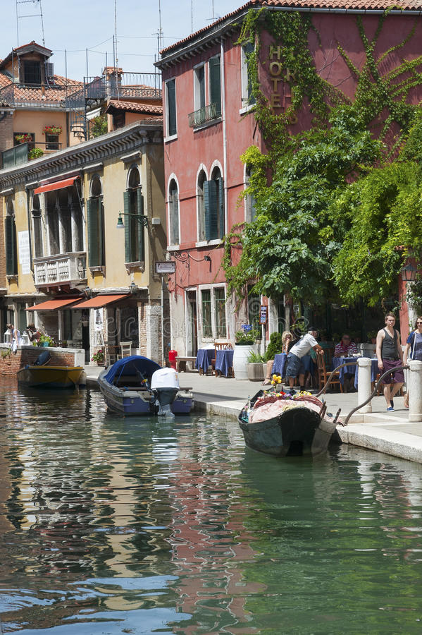 ITALY, VENICE - JULY 12, 2014: View of the streets of Venice, pa. Rked boats and leisure travelers royalty free stock images