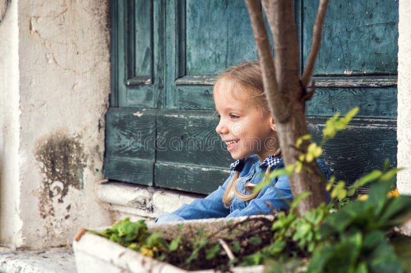 italy venice Lite spelar den charmiga flickan i en blå klänning i en gammal Venetian borggård, skrattar royaltyfri foto