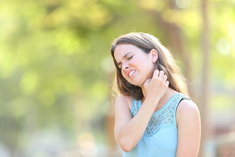 Itching di sofferenza della donna graffiando collo immagini stock