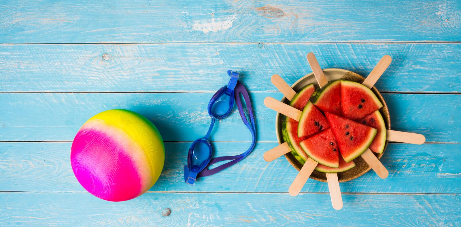 Item for summer. Watermelon cut into pieces Plugged in with a stick, making it like ice cream, stacked in a side dish with swimming goggles and ball for water royalty free stock photography