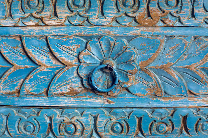 Item wooden wardrobe painted in blue paint pattern. And carving with flower and leaves stock photos