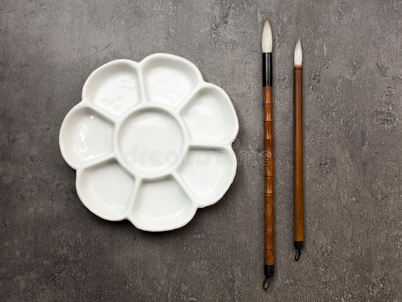 Items for drawing sumi-e, Chinese brushes, ceramic palette. Items for drawing Japanese watercolor sumi-e, Chinese brushes of goat hair, ceramic palette on gray stock photography