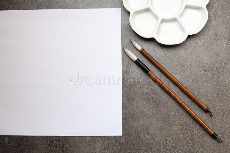 Items for drawing sumi-e, rice paper, Chinese brushes, ceramic p. Items for drawing Japanese watercolor sumi-e, rice paper, Chinese brushes of goat hair, ceramic stock photography