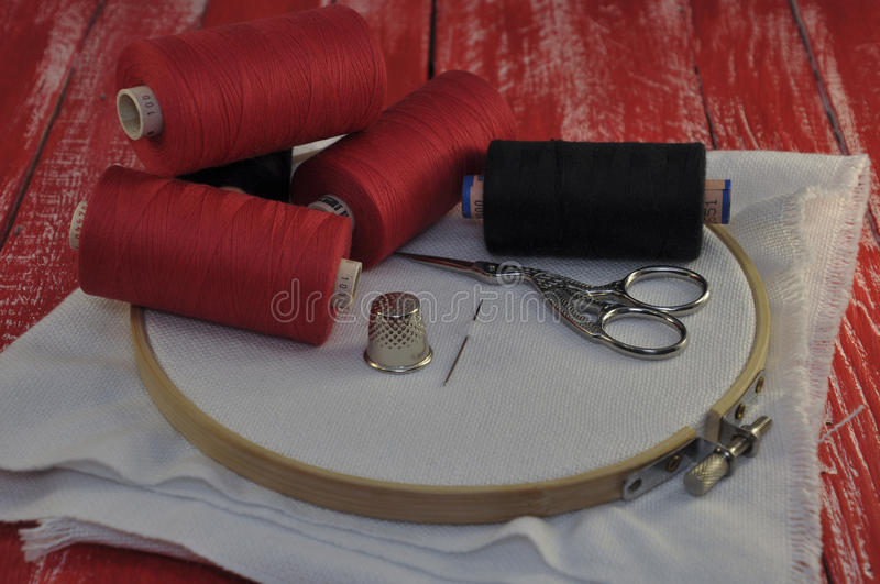 Items for sewing and embroidery. On the background of a red wooden table stock images