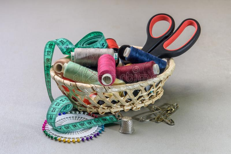 Items for sewing in the basket. Items for sewing, thread, needle, scissors folded in a basket royalty free stock photography