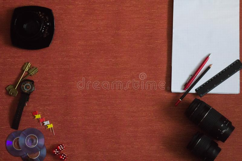 Items are on the table. On the table are a Cup of coffee, a camera, a lens and a pen, a pencil and a lighter, a notebook and a wristwatch, paper clips and royalty free stock photos