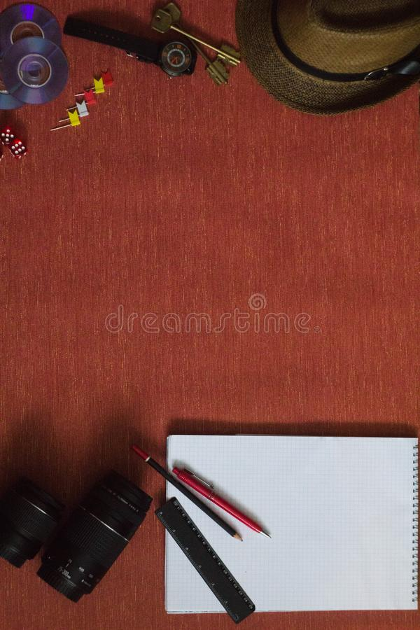 Items are on the table. On the table are a Cup of coffee, a camera, a lens and a pen, a pencil and a lighter, a notebook and a wristwatch, paper clips and stock photos