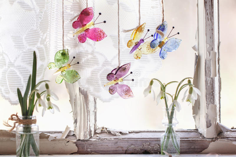 Iterior window with glass butterflies and snowdrops stock images