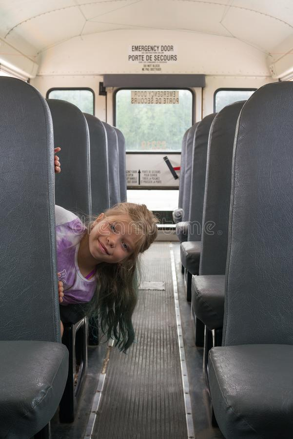 IThe young Caucasian blond girls is coming out from the bus`s seat. She is sitting in a school-bus. stock photo