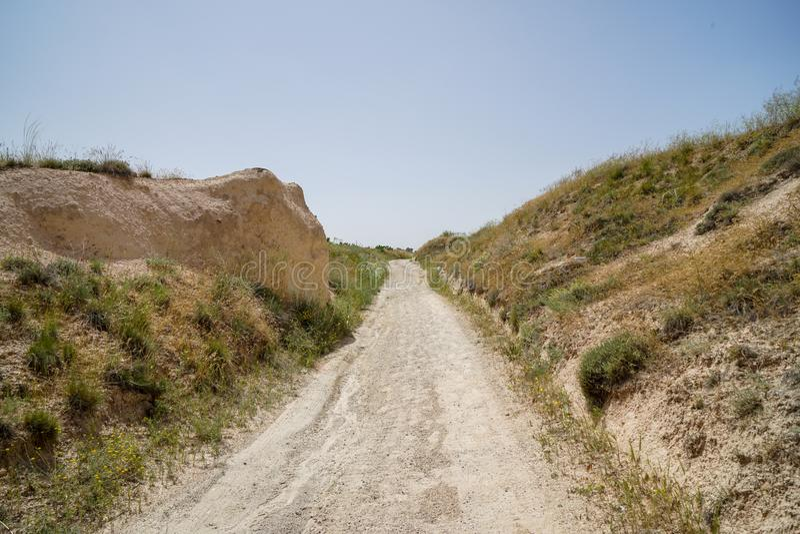 Itinerario ruvido non pavimentato di camminata della traccia della sabbia attraverso paesaggio della valle rossa antica secca con fotografia stock libera da diritti