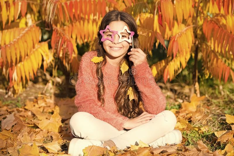Its all a masquerade. Little child hold fake glasses on face. Girl child have fun on autumn day. Little child full of royalty free stock photo