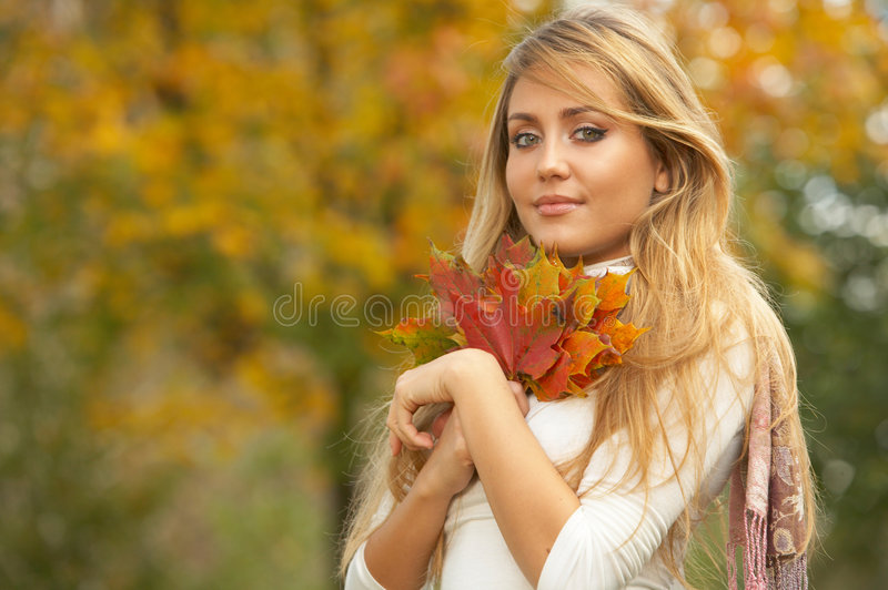 Its Autumn!. 20-25 years old beautiful woman portrait holding leafs in natural autumn outdoors stock photography