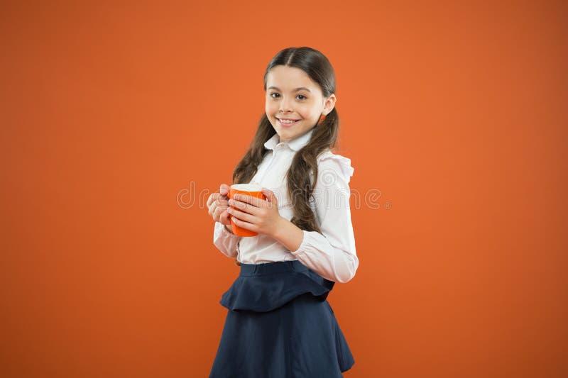 Its break time. Cute schoolgirl enjoying school break on orange background. Little girl having tea break in school stock photo