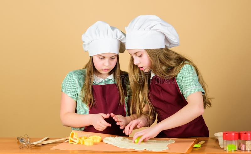 Its not the gods who bake pots. Small children rolling paste to bake pies. Adorable little girls preparing dough in bake royalty free stock photo