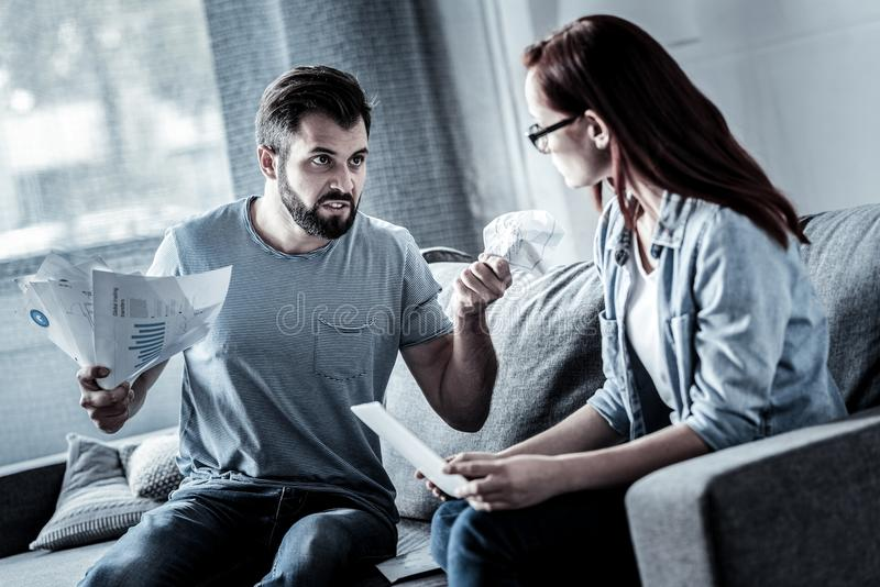 Angry stressful man holding papers and looking at woman. royalty free stock photography