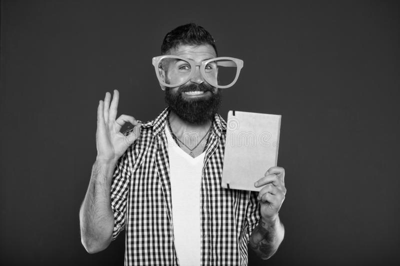 Its ok. Study nerd inviting for reading book. University male student with lecture notes. Bearded man in party glasses royalty free stock image