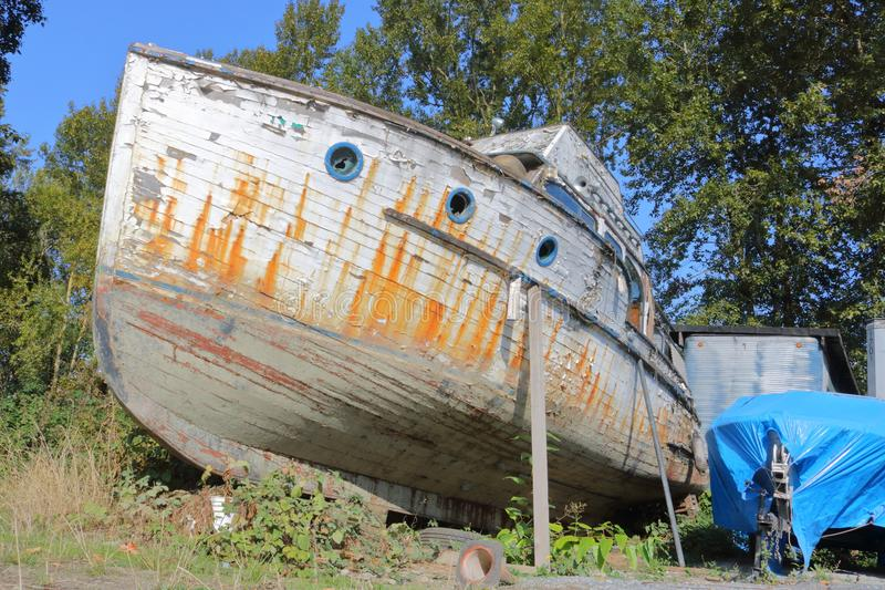 Derelict Wooden Boat. With its paint peeling and hull in disrepair, a wooden boat, forgotten and abandoned, sits cradled on supports stock image