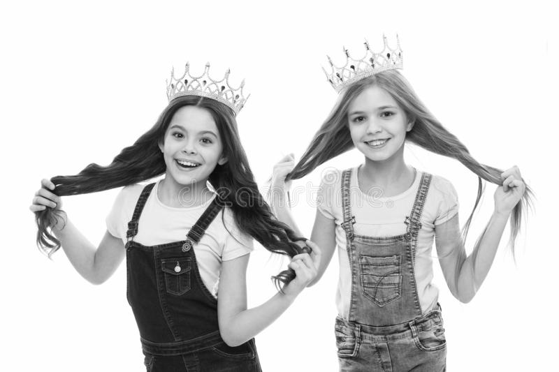 Its pride that drives them. Adorable little princesses in crowns with long hair source of their pride. Cute small girls royalty free stock images