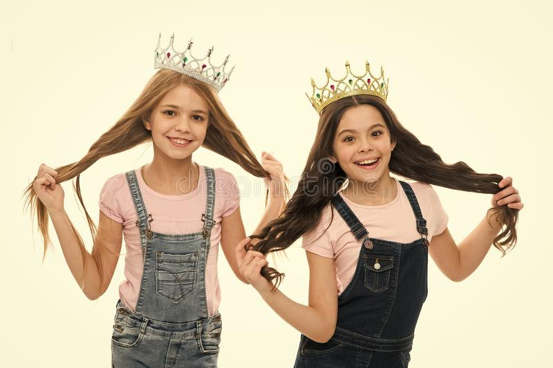 Its pride that drives them. Adorable little princesses in crowns with long hair source of their pride. Cute small girls royalty free stock image
