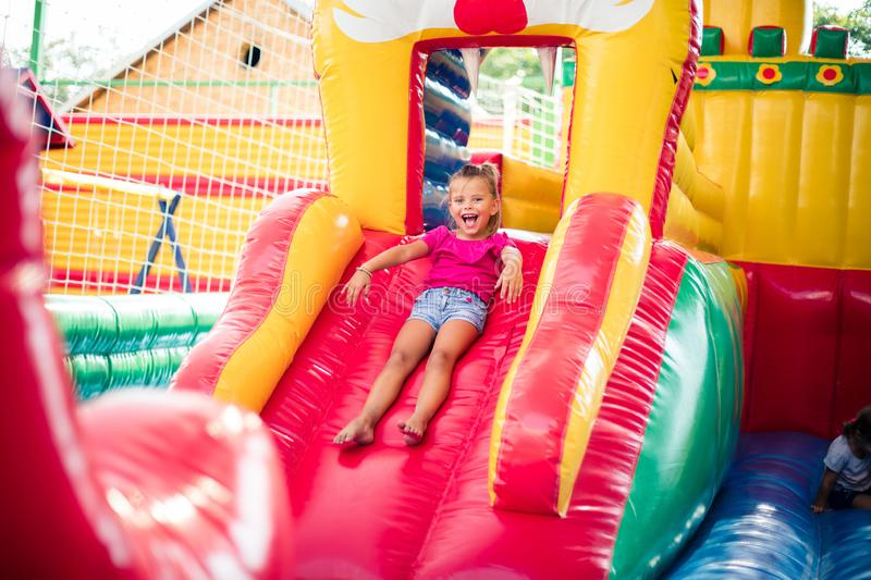 Its time for fun. Little girl playing in playground and sliding. Space for copy royalty free stock photo