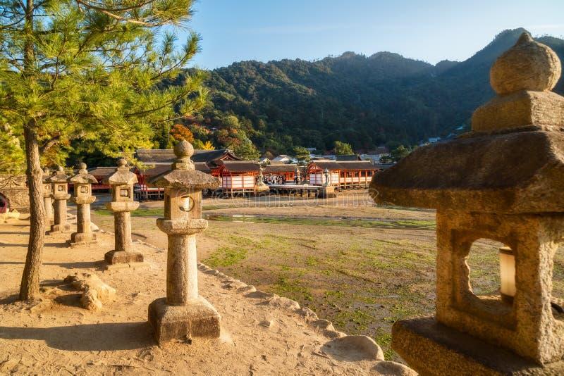 Itsukushima shrine with stone lanterns in the foreground on Miyajima Island in Japan. Itsukushima Shinto shrine with stone lanterns in the foreground on Miyajima stock photos