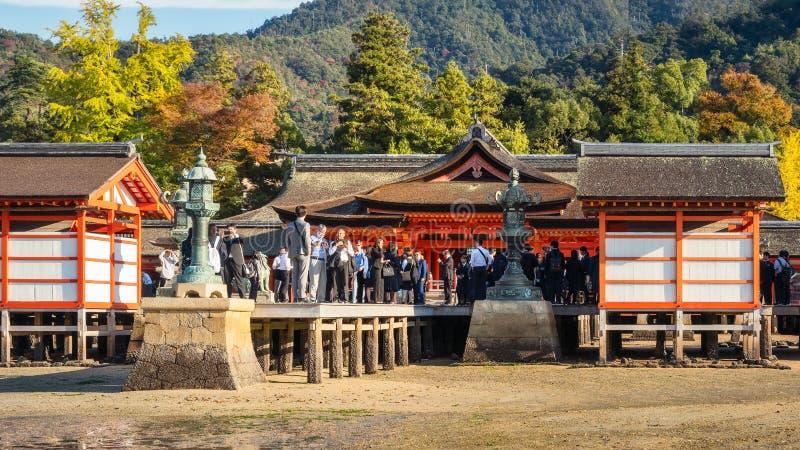 Tourists at the main temple at Itsukushima Shrine on Miyajima island, Japan. Itsukushima Shrine, Miyajima, Japan - November 7, 2018: Tourists walk around the royalty free stock photography