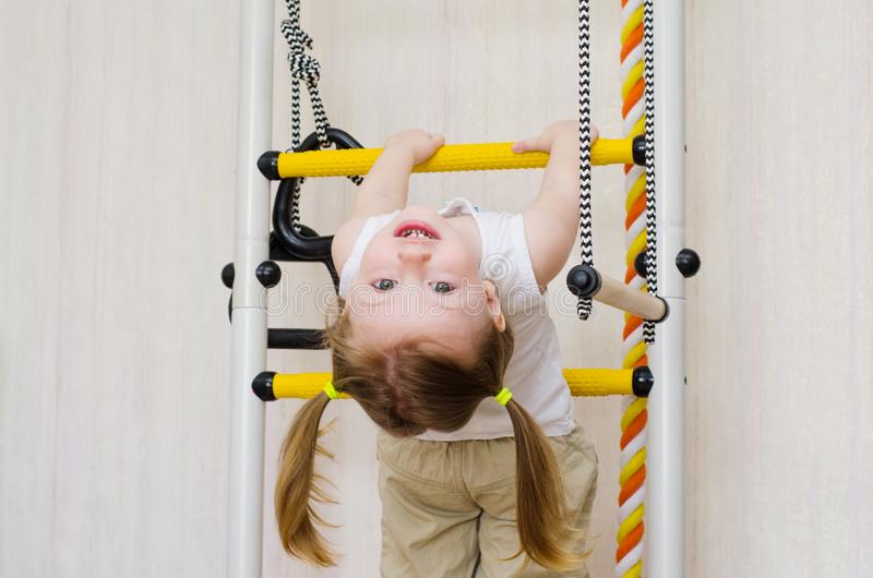 Ittle girl hangs on the stairs upside down royalty free stock photo