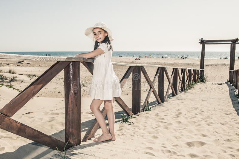 Little girl with hat leaning against wooden railing on the beach stock photo