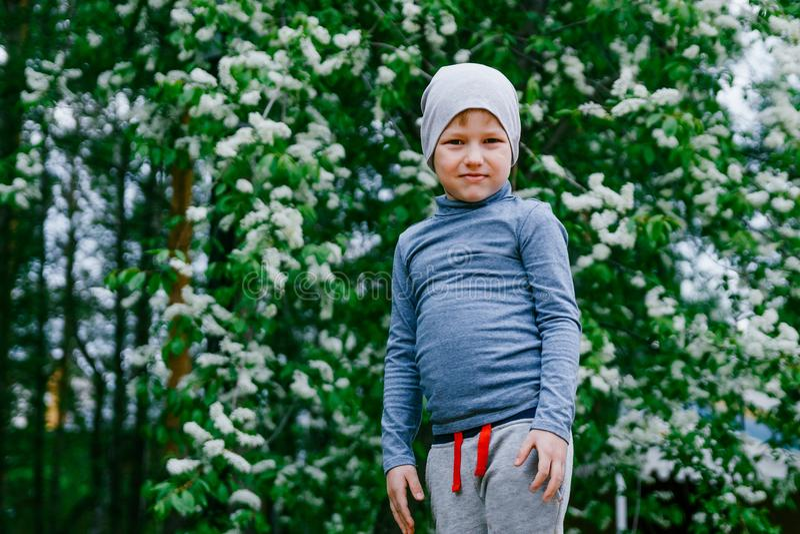 Ittle-Junge auf einem Hintergrund der blühenden Kirsche lizenzfreie stockbilder