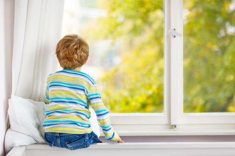 Ittle kid boy sitting near window and looking on autumn trees royalty free stock photos