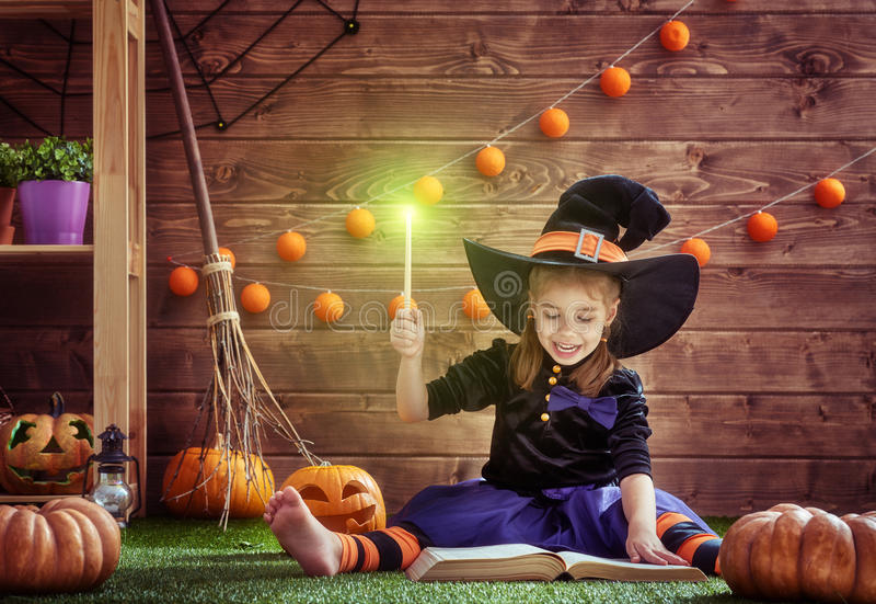 Ittle witch with a magic wand. Happy Halloween! Cute cheerful little witch with a magic wand and book of spells. Beautiful child girl in witch costume sitting on stock photography