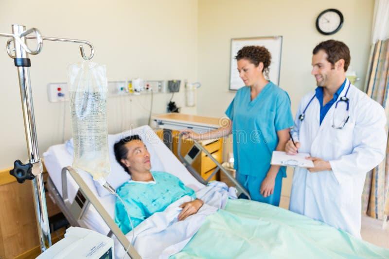 IV сумка на штанге при медицинская бригада смотря пациента стоковое фото