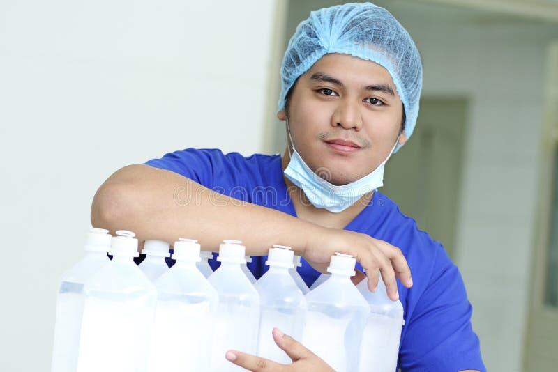 IV Fluids Treatment. Portrait of a handsome young male asian nurse with IV fluids stock image