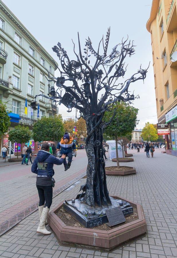 Ivano-Frankivsk, Ucrânia - 17 de outubro de 2015: A criança monta uma árvore forjada do metal da felicidade imagens de stock royalty free