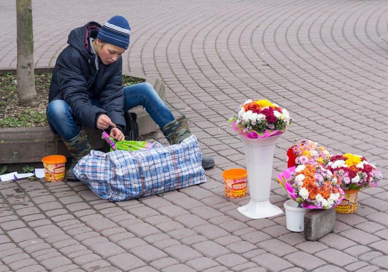 Ivano-Frankivsk Ukraina, Październik, - 17, 2015: Nastolatek siedzi na chodniczku sprzedaje kwiaty zdjęcia stock