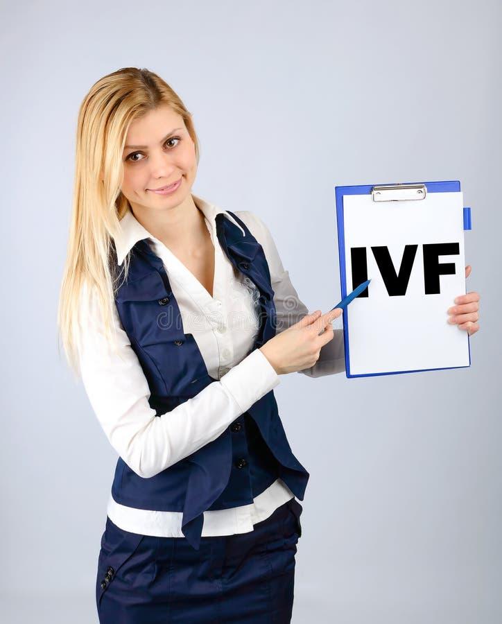 IVF En kvinna visar på hennes minnestavla befruktningen för förkortningen in vitro fotografering för bildbyråer