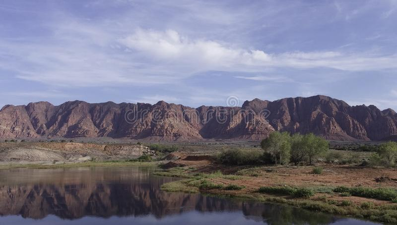 Ivins Lake with red sandstone mountains in the background in Utah. Ivins Lake with red sandstone mountains and clouds in the background in Utah stock photos