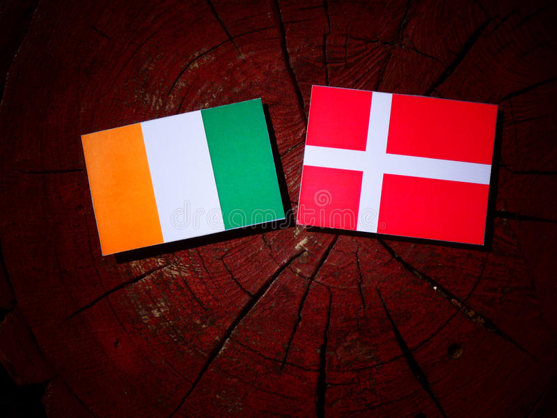 Ivory Coast flag with Danish flag on a tree stump isolated royalty free stock photography