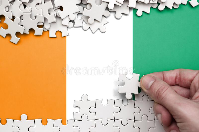 Ivory Coast flag is depicted on a table on which the human hand folds a puzzle of white color.  royalty free stock photos