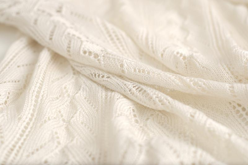 Ivory color crochet sweater. Texture detail close up with high key lighting. Ivory color crochet sweater. Texture detail close up. Studio shot stock photography