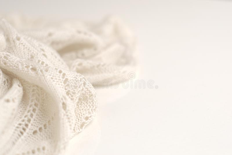 Ivory color crochet sweater on white background. Texture detail close up. Studio shot stock image