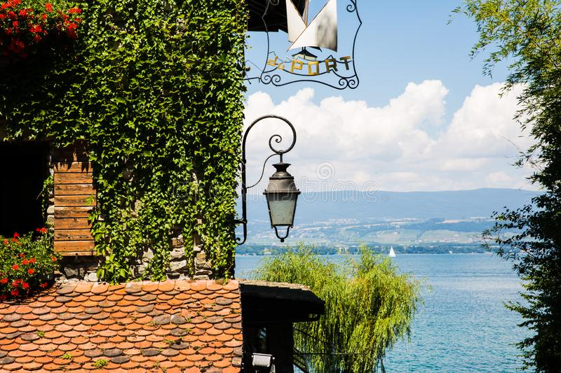 Ivy Covered Stone House with Red Flowers, Boats and Lake on a Sunny Day.  royalty free stock photography